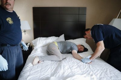 Man-Overdosed-On-Bed-EMTs-Assisting