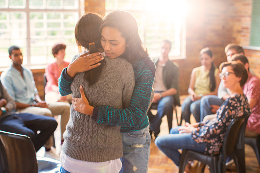 Two Women Hugging in Group Therapy Setting